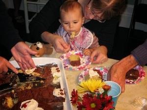 Graciela's first taste of birthday cake, baked by Grandma.